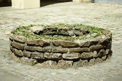 Forntida rund stentegelsten väl, lite dekorerat Arkivbilder