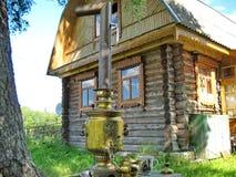 Forntida samovar i bakgrunden av en bykoja Samovar - en apparat för koka vatten och att förbereda te Tebjudning på gatan royaltyfri foto
