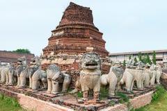 Forntida skulpturer omger en Stupa på Wat Thammikarat i Ayutth Arkivbild