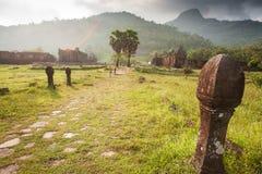 Forntida skulptursandstenpelare på vaten Phou, södra Laos Koppla ihop turister, berget och den härliga solen som ställer in bakgr royaltyfri foto