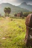 Forntida skulptursandstenpelare på vaten Phou, södra Laos Koppla ihop turister, berget och den härliga solen som ställer in bakgr royaltyfri bild