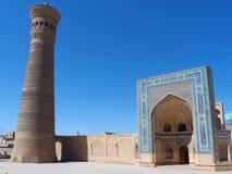 Forntida stad under blå himmel: fyrkant med minarettornet och moskéingången Arkivfoto