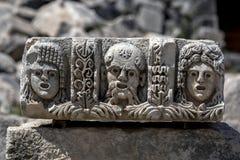 Forntida stenhuggeriarbete på Myra i Demre i Turkiet som visar tre mänskliga framsidor Royaltyfri Fotografi
