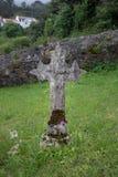 Forntida stenkors av en gravsten i en lantlig kyrkog?rd mycket av gr?s i Galicia, Spanien royaltyfria bilder