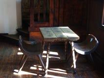 Forntida stolar och bordlägger Arkivfoto