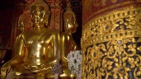 Forntida stora förgyllda Buddha som placeras på en lyftt plattform inom Wat Phumin Temple lager videofilmer