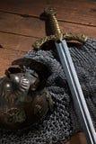 Forntida svärd, chain harnesk och soldatens hjälm med horn Royaltyfri Fotografi