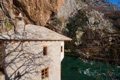 Forntida tegelstenbyggnad av den historiska Sufi kloster Blagaj Tekke med en flod och bergen omkring arkivbilder