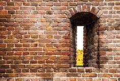 Forntida tegelstenvägg av slotten med kryphålet som bakgrund Royaltyfri Bild