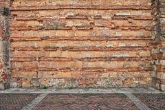 Forntida tegelstenvägg och stenlagd trottoar Fotografering för Bildbyråer