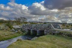 Forntida 13th århundradestenbro på Dartmoor England UK fotografering för bildbyråer