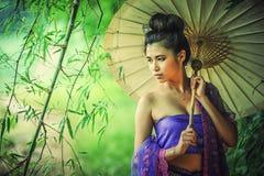 Forntida thailändsk kvinna i traditionell klänning av Thailand med tappning Arkivbild