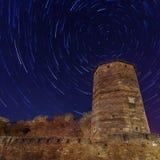 Forntida torn i bakgrundsstartrailsna Arkivfoto