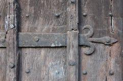 Forntida trädörr med fransk liljaironworken royaltyfri bild