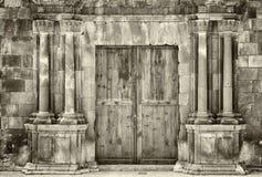 Forntida trädubbla dörrar för monokrom sepia i en gammal stenbyggnad med att smula utsmyckade kolonner som omger ingången arkivbilder