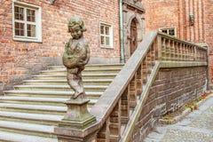 Forntida trappuppgång med en pojkestaty Arkivbild