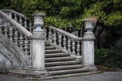 Forntida trappuppgång med stenbaluster mot bakgrunden av grön vegetation royaltyfri fotografi