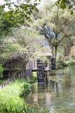 Forntida vattenhjul inom den fridfulla och sceniska floden Royaltyfria Bilder
