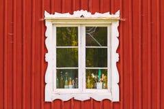 Forntida vitt fönster i ett rött träsvenskhus Royaltyfri Foto