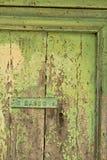 Forntida ytterdörr med ljust - grön målad platta royaltyfri bild
