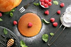Fornuis met heerlijke pannekoeken op een zwarte achtergrond stock foto's
