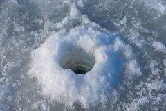 Foro del ghiaccio perforato con una coclea di pesca fotografia stock