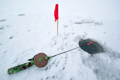 Foro del ghiaccio in pesca e barretta di inverno Fotografia Stock