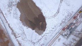 Foro di scavatura dell'escavatore di estrazione mineraria in terra nevosa sulla vista del fuco di zona industriale video d archivio