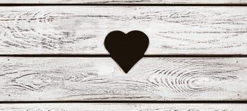 Foro a forma di del cuore nel legno fotografie stock libere da diritti