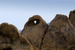 Foro a forma di del cuore nella roccia Immagini Stock