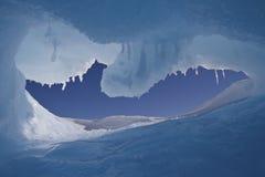 Foro in un iceberg con una vista del cielo antartico Immagine Stock