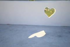 Foro verde del cuore in parete bianca immagine stock