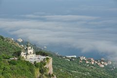 Foros Church Over the Clouds. FOROS, CRIMEA, RUSSIA - View from Baidarsky Pass on the Church of Christ`s Resurrection raising on the Red Cliff Krasnaya Skala stock photo