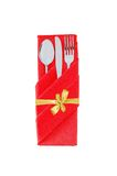 Forquilha, colher e faca no pano vermelho com a curva dourada isolada em w Fotografia de Stock