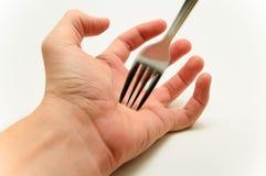 Forquilha cortante uma palma da mão no fundo branco Imagem de Stock