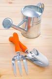 Forquilha da pá de pedreiro das ferramentas e lata molhando Fotografia de Stock Royalty Free