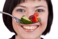 Forquilha da terra arrendada da mulher com salada imagem de stock