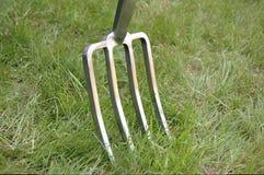 Forquilha do jardim introduzida no gramado imagens de stock royalty free