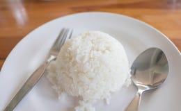 Forquilha e colher cozinhadas do arroz no prato branco Imagens de Stock Royalty Free