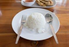 Forquilha e colher cozinhadas do arroz no prato branco Fotos de Stock Royalty Free
