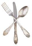 A forquilha e a colher de prata velhas da faca cruzaram-se isolado Imagens de Stock