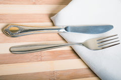 Forquilha e faca em um guardanapo branco e em uma placa de madeira Imagem de Stock Royalty Free