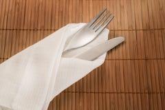 Forquilha e faca na matéria têxtil branca no fundo de bambu Fotos de Stock Royalty Free