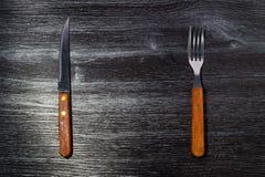 Forquilha e faca no fundo de madeira da textura Fotografia de Stock