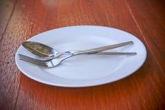 Forquilha e placa branca em uma tabela de madeira Fotografia de Stock