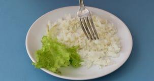 Forquilha e placa com arroz e alface filme