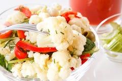 A forquilha guarda uma parte de couve-flor sobre uma placa da salada fresca com couve-flor, tomates e verdes Imagens de Stock Royalty Free
