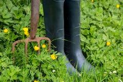 Forquilha velha do jardim e botas de borracha com ervas daninhas e as flores selvagens imagens de stock