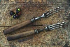 Forquilhas antigas em uma placa de madeira, um ramo do corinto preto Fotos de Stock