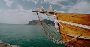 Forraje de una nave de madera contra el contexto de las montañas y del mar almacen de video